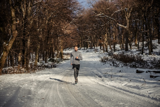 Sportsman running in nature on snow at winter