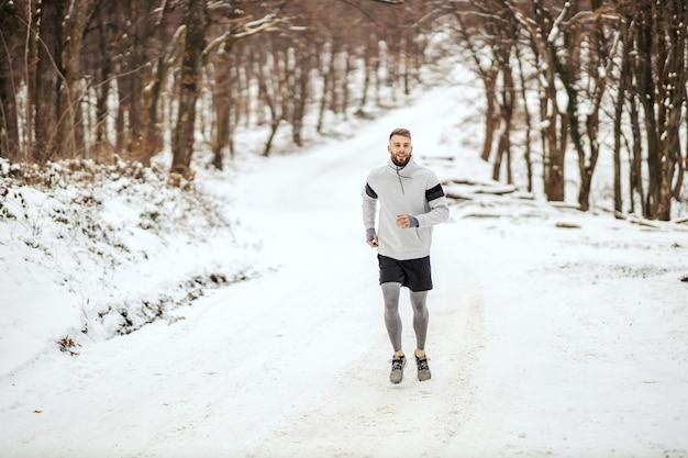 겨울에 숲에서 눈 덮인 길을 달리는 스포츠맨. 겨울 스포츠, 건강한 습관, 야외 피트니스