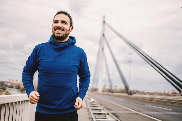曇りの日、橋の上を走るスポーツマン。