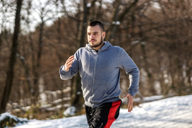 Sportsman running on snowy path in nature at sunny winter day. winter fitness, cardio exercises, healthy habits