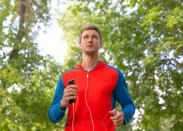 森の道をスポーツマンが走っています。彼はイヤホンで音楽を聴いています。スポーツのコンセプトと健康的なライフスタイル。