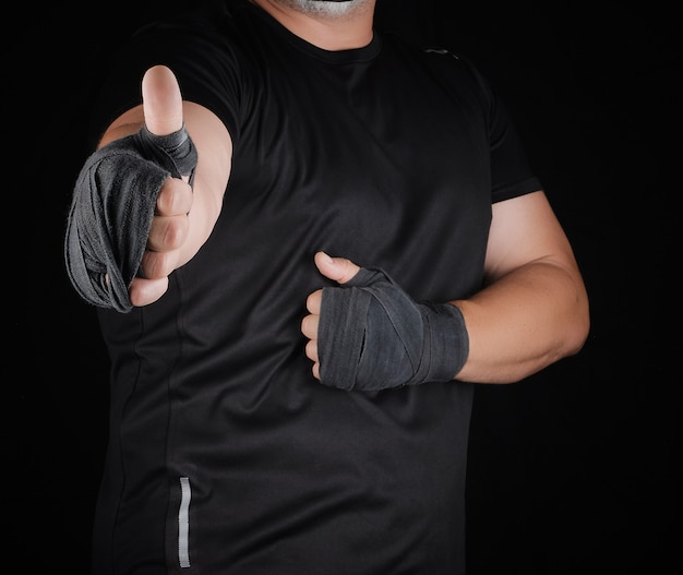 Sportsman's hands wrapped in black elastic sports bandage show a like