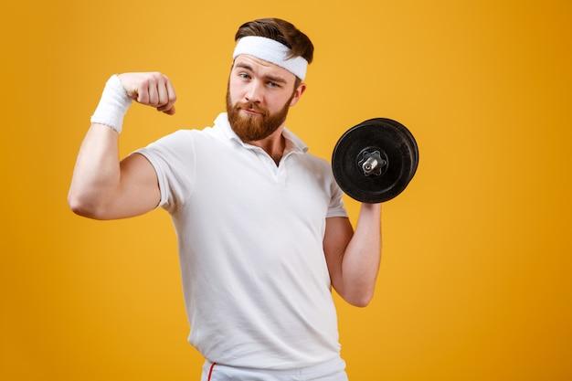 Спортсмен показывает бицепс и держит гантель
