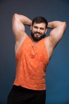 Спортсмен показывает свои мышцы и держит гантель.
