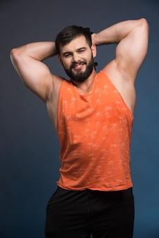 Sportivo che mostra i suoi muscoli e che tiene un manubrio.