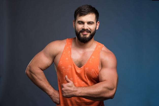 Спортсмен показывает свои мышцы на синей стене.