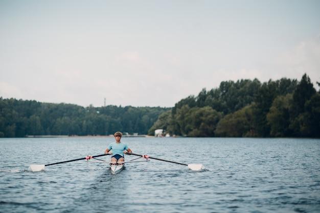 スポーツマンシングルスカルマン漕ぎ手が競技ボートレガッタの準備をします。オリンピックスポーツ。
