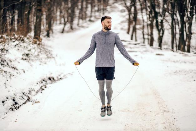 Спортсмен прыгает через скакалку на природе в снежный зимний день. зимний фитнес, здоровый образ жизни, кардио упражнения