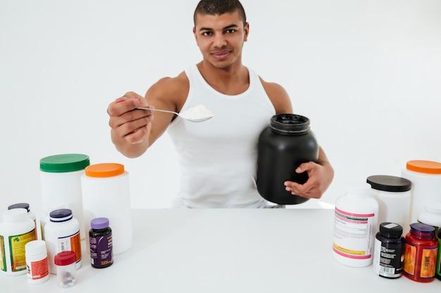 ビタミンを保持している白い壁に立っているスポーツマン