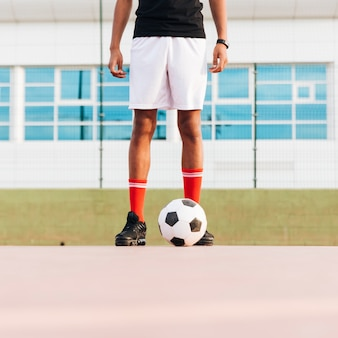Sportsman standing with football and preparing for game at stadium