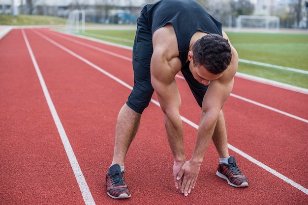 Sportsman stretching hands at the stadium