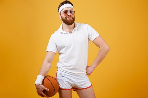Sportivo in occhiali da sole che tiene pallacanestro