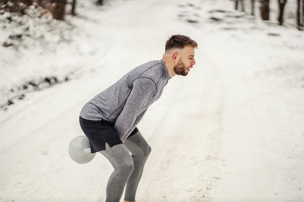 冬の雪道で自然の中で立っている間ケトルベルを振るスポーツマン。ボディービル、ウィンタースポーツ、フィットネス