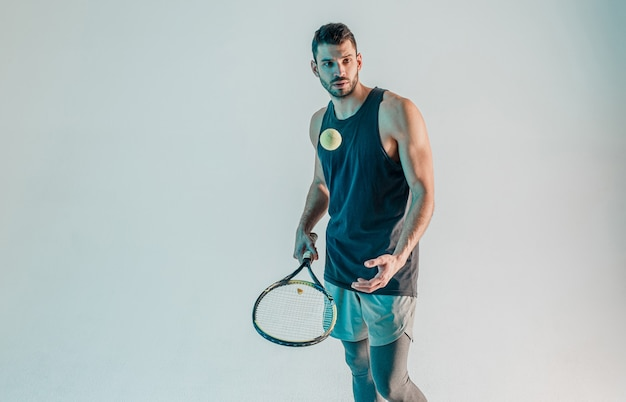 Sportsman throw up tennis ball and holding racquet. young bearded european tennis player is concentrated on game. isolated on gray background with turquoise light. studio shoot. copy space