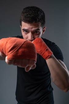 Sportsman throwing right straight punch with hand in wrist wraps