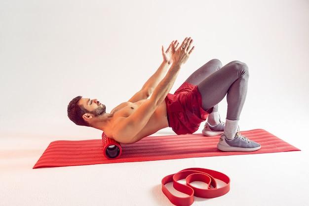 Спортсмен тренирует мышцы живота на фитнес-коврике
