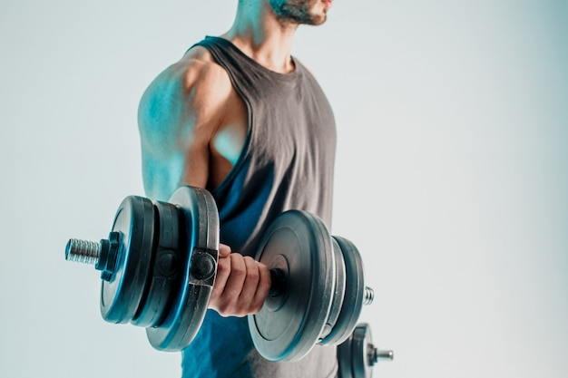 Спортсмен тренирует мышцы бицепса с гантелями. бородатый мужчина носит спортивную форму. изолированные на бирюзовом фоне. студийная съемка. копировать пространство