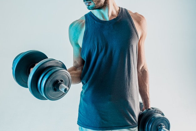 Спортсмен тренирует мышцы бицепса с гантелями. бородатый мужчина носит спортивную форму. изолированные на бирюзовом фоне. студийная съемка