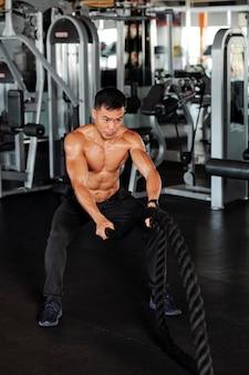 バトルロープを使ってトレーニングするスポーツマン