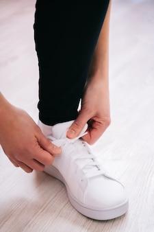 Sportsman tying white sneaker on light background