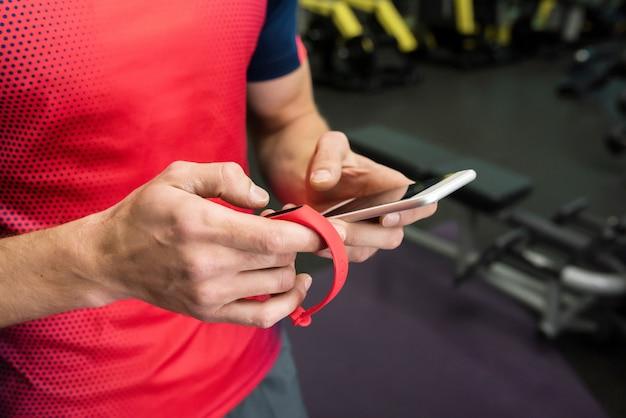 Спортсмен с помощью фитнес-устройства в тренажерном зале
