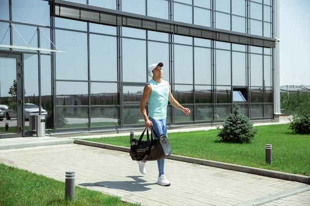 Sportsman walking down against modern glassed building, airport in megapolis in summer's day.