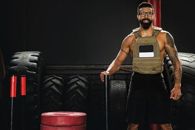 ジムでのトレーニング中にウェイトベストを着ているスポーツマン