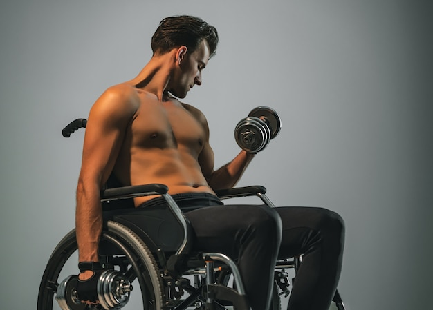 The sportsman in wheelchair works with dumbbell