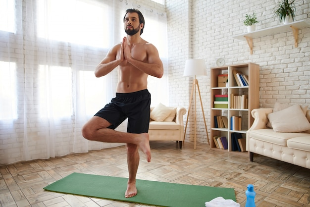 Sportsman with bare torso practicing advanced yoga at home.