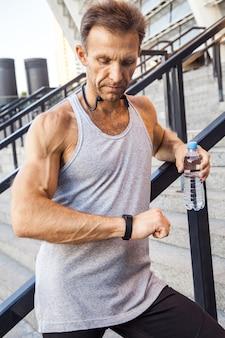 물 한 병을 든 스포츠맨이 달리기 후 스마트 시계를 확인하고 쉬고 있습니다. 피트 니스, 스포츠, 운동 및 사람들이 건강한 라이프 스타일 개념.