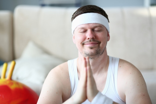 Sportsman with closed eyes smiling face portrait. bearded man doing yoga meditation with hands together. peaceful indoor sport.
