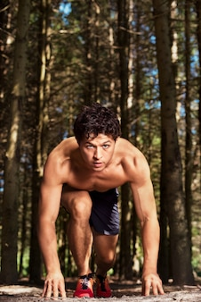 Sportsman with a naked torso and on concentrated face ready to go, before running through the forest
