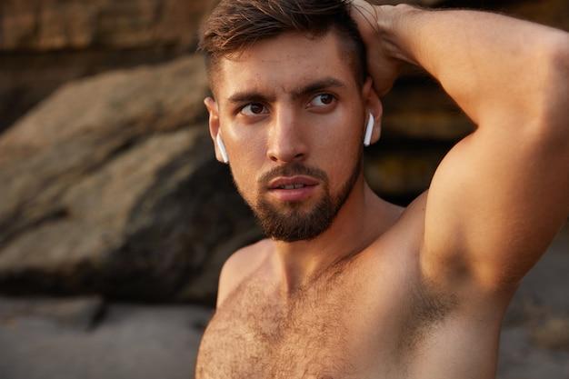 真面目な顔つきのスポーツマンは、手を頭の後ろに置き、海岸線に対して半分裸でポーズをとる