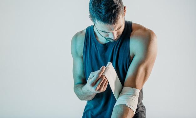Спортсмен, перевязавший медицинскую повязку на руке. молодой бородатый европейский мужчина носит спортивную форму. понятие о спортивной травме. изолированные на бирюзовом фоне. студийная съемка. копировать пространство
