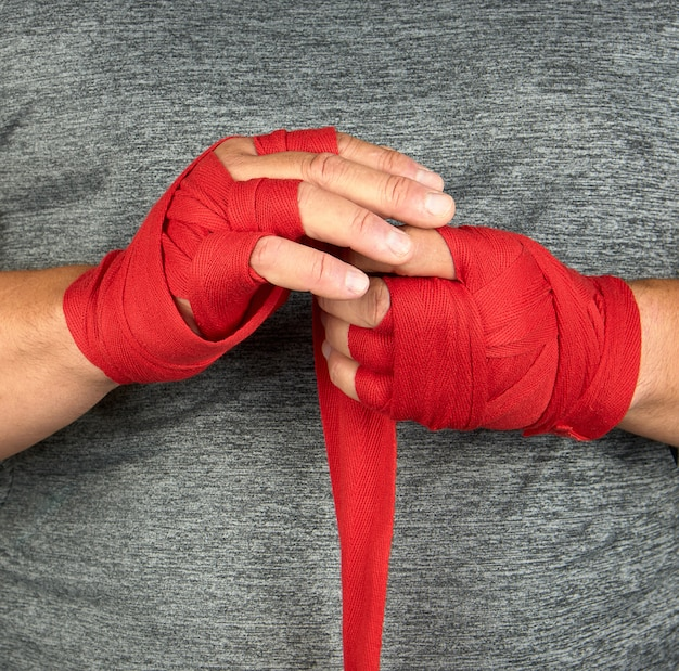 Sportsmanã¢â€â™s hands wrapped in a red elastic sports bandage