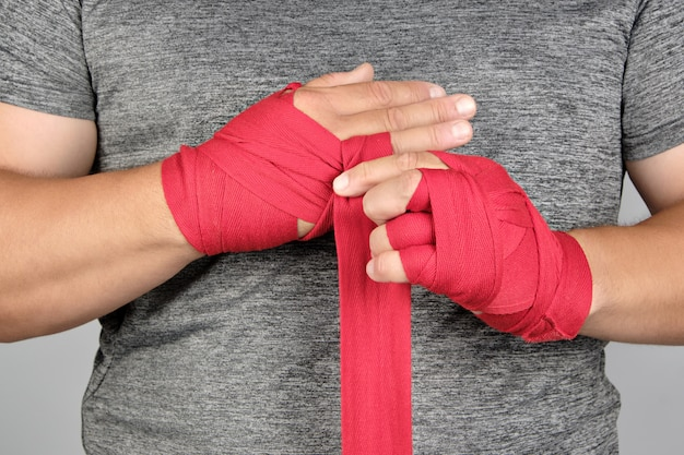 Sportsman's hands wrapped in a red elastic sports bandage
