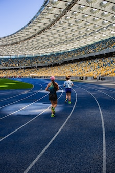 Sportsmans runnings on the empty blue running track at the olympic stadium against the background of empty stands