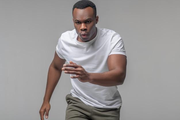 운동가 정신. 그의 팔을 올바르게 흔들며 호흡을 실행하는 흰색 티셔츠에 활기찬 집중된 젊은 흑인