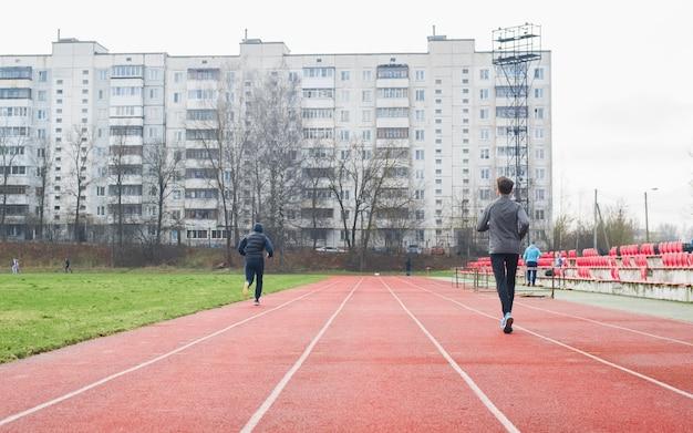外のスタジアムでのスポーツマンアマチュアランナー、背面図。アウトドアトレーニングの人々、アクティブなライフスタイル。