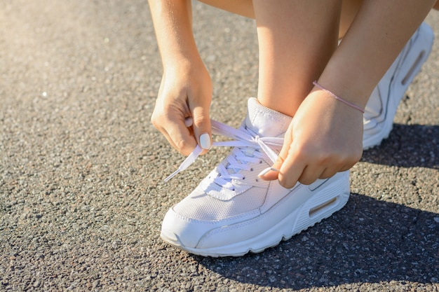 Sportsmen girl in white sneakers stopped on the road and typing shoelaces while jogging workout in the evening.
