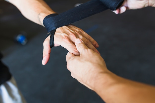 Sportsmen taping hand with band