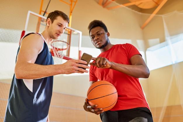 Спортсмены используют смартфон на баскетбольной площадке