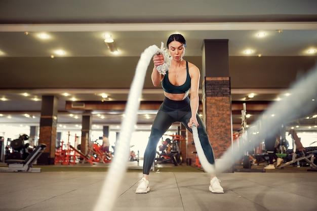 Кавказский подходит женщина, одетая в sportsoutfit делает тренировки с боевыми веревками в тренажерном зале.