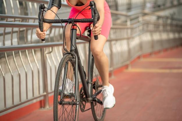 Sportsperson。明るいスポーツウェアと自転車で保護ヘルメットの女の子