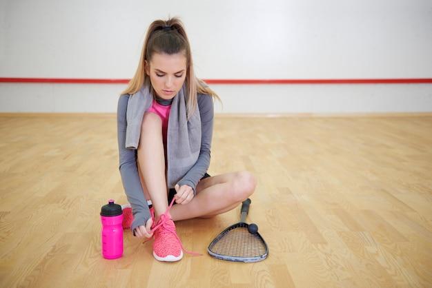 Спортсмен, завязывающий спортивную обувь во время короткого перерыва