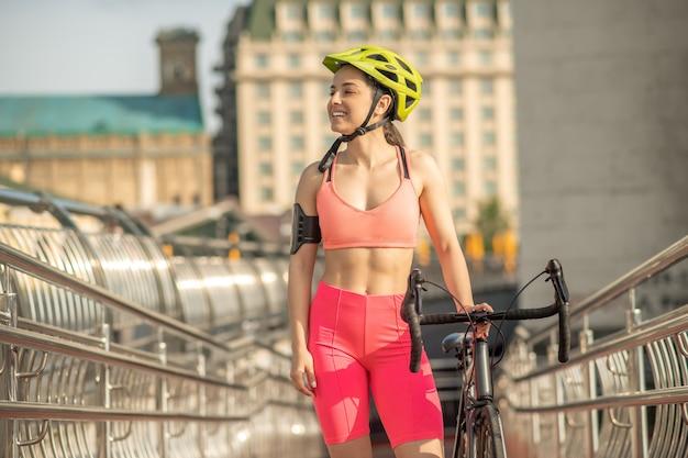 スポーツ選手。明るいスポーツウェアと自転車と保護ヘルメットの若いかわいい女の子