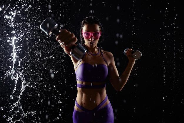 Красивая маленькая девочка в фиолетовой sportswear представляет с гантелями в студии aqua. капли воды распространились по ее телу. идеальная фигура на фоне брызг воды