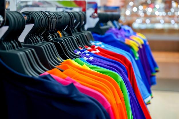 Спортивная одежда висит на бельевой веревке в спортивном магазине.
