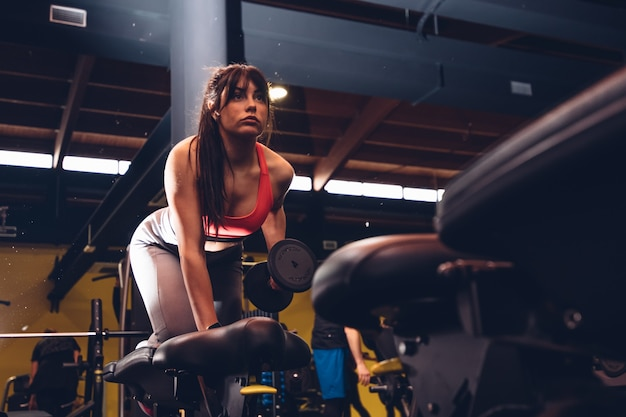 Sportswear woman lifting weight at the gym