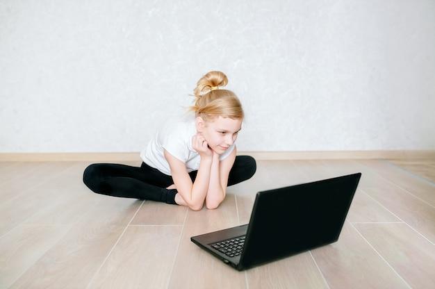 Милая маленькая девочка в sportswear смотря онлайн видео на компьтер-книжке и делая тренировки фитнеса дома. дистанционное обучение с личным тренером, социальная дистанция или самоизоляция, концепция онлайн-обучения